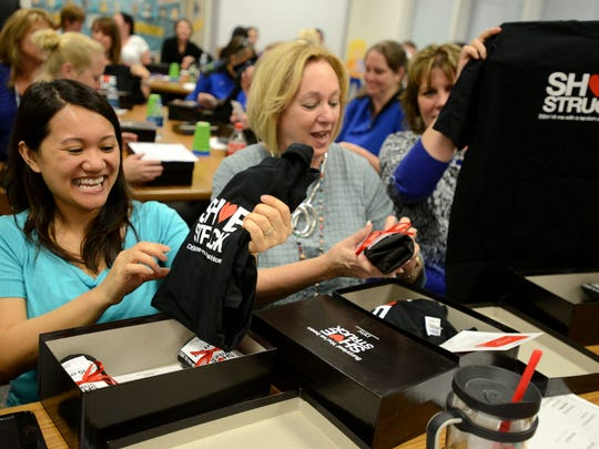 """Blue Angels Elementary School teachers Nguyet Pham, left, and Carol Hudspheth open shoe boxes as each of the school's faculty and staff were each given a pair of shoes during a surprise event """"Shoe Struck"""" on Wednesday from Rose Designer Shoe Warehouse. The shoe company noticed fith grade teacher Angie Rose's love for fashionable shoes after she was featured in Bella Magazine. They decided to make a surpise visit during a faculty meeting in appreciation of the teachers' hard work with the students."""