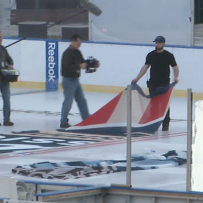 Crews lay install the Center Ice logo on the Winter