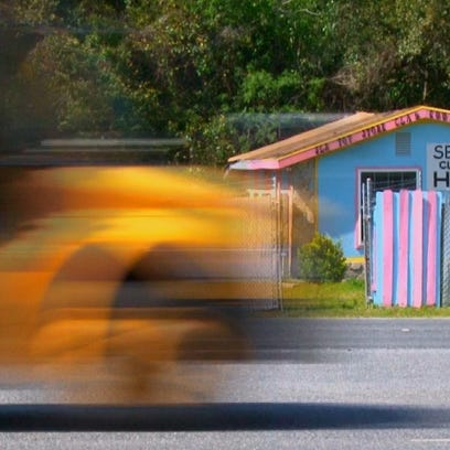 "School bus passes by ""Sex & Buds"" Toy Store in Middleburg,"