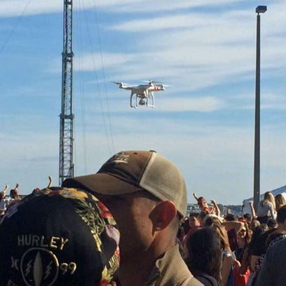 Remote-controlled drone hovers over the crowd at the