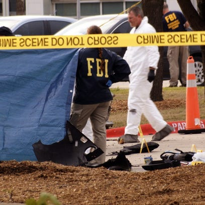 FBI agents view the area where the shooting suspects