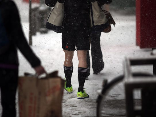 NEW YORK, NY - JANUARY 21:  A man walks in shorts in Manhattan during a snowstorm that is moving through the Northeast on January 21, 2014 in New York City. Along with dropping arctic tempertures the storm is expected to bring three to five inches by nightfall, with another four to six inches falling overnight.  (Photo by Spencer Platt/Getty Images)