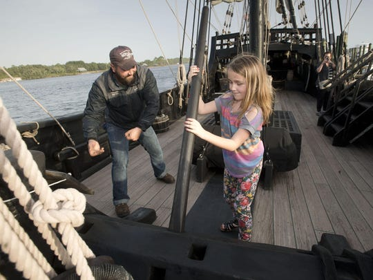 Gus Kodros, first mate on the Nina, right, gives Kinley Gillihan, left, first-hand experience of life aboard the sailing ship during her visit to the replica of the 15th-century vessel Wednesday afternoon Dec. 23, 2015. The recreation of the Nina and Pinta are docked at the Perdido Key Oyster Bar and Restaurant until early January.