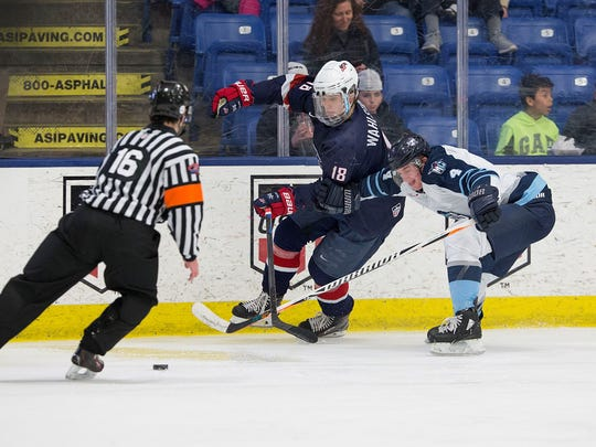 Digging for the puck Friday night is Team USA forward Oliver Wahlstrom (18). He had two assists in a 6-4 victory over Madison.