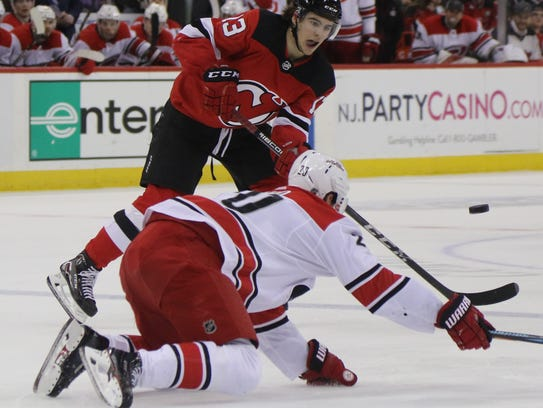 Nico Hischier of the Devils passes the puck past a