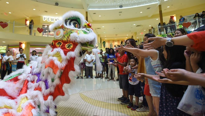 "Audience members gather to participate in the traditional custom of ""Cai Qing"" during a performance by the Chinese School of Guam's Lion Dance Team at the Agana Shopping Center on Feb. 18, 2018. The Chinese School of Guam Lion Dance Team performed throughout the Agana Shopping Center, interacting with shoppers, in celebration of the Chinese New year."