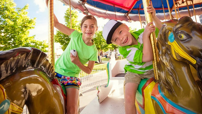 Two cute kids enjoying a ride on a fun carnival carousel. A happy girl and boy are Smiling and having fun together at the summer carnival