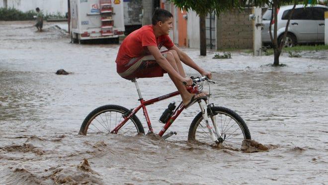 A resident rides a bike through a flooded street in Villa de Coral, Mexico, Wednesday Oct. 12, 2011.
