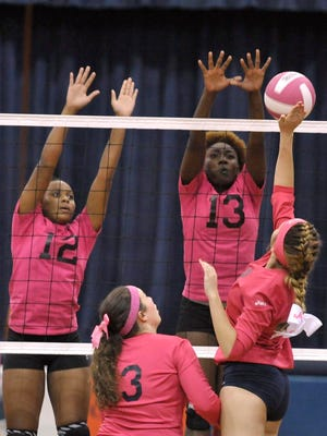Ava Battaglia, No. 8 of the Escambia High Gators, tries to tip this shot in past Rakell Watts, No. 12, and Malainna White, No. 13, of the Pensacola High Tigers during their game Thursday night at EHS.  The Tigers went on to win the match in three games, 25-7, 25-13 and 25-21.