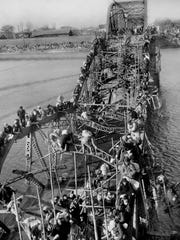 Residents from Pyongyang, North Korea, and refugees from other areas crawl perilously over shattered girders of the city's bridge, as they flee south across the Taedong River to escape the advance of Chinese communist troops Dec. 4, 1950.