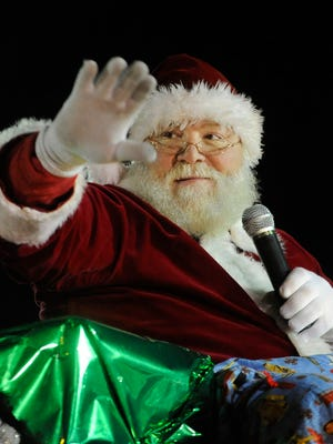 Santa Claus waves to the crowd as he heads up South Eighth Street during the Lakeshore Holiday Parade in 2014.