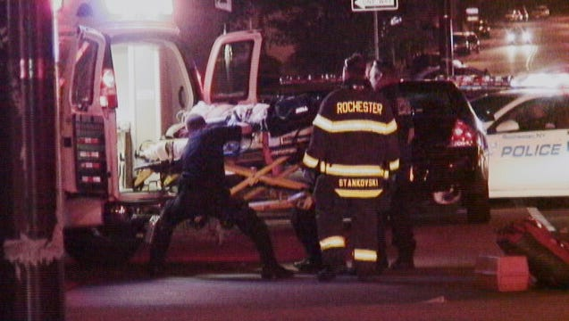 One of the victims of Sunday morning's shootings on South Plymouth Avenue is lifted into an ambulance at the scene.