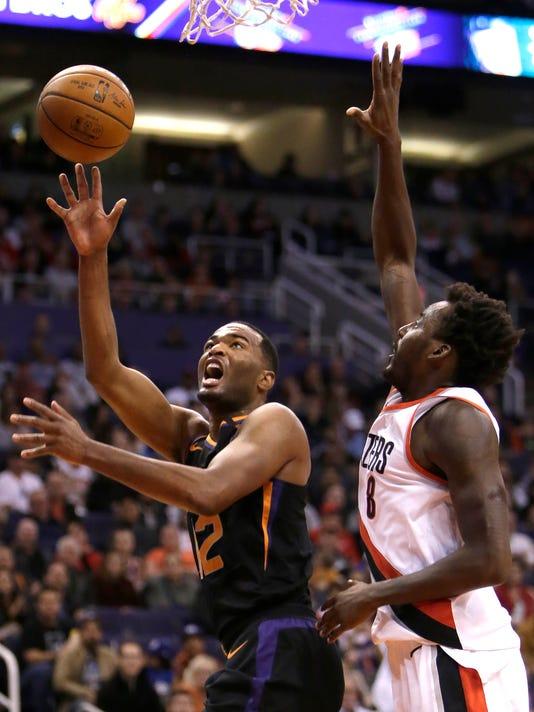 Phoenix Suns forward TJ Warren (12) shoots in front of Portland Trail Blazers forward Al-Farouq Aminu during the second half of an NBA basketball game Saturday, Feb. 24, 2018, in Phoenix. The Trail Blazers defeated the Suns 106-104. (AP Photo/Rick Scuteri)