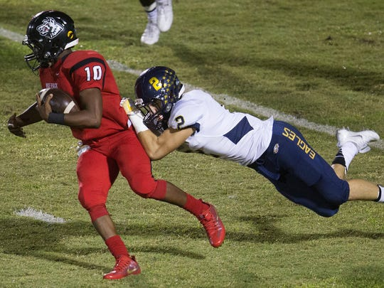 South Fort Myers High School's Kam Crawford breaks free from Naples' Andre Eaton during second quarter play Friday at South Fort Myers High School. Naples beat South 39-12.