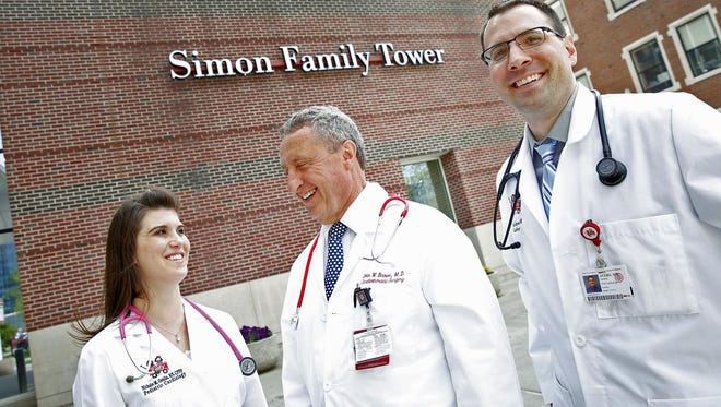 Nichole Gralia, from left, Dr. John Brown, and Dr. Mark Ayers, right, stand in front of Riley Hospital for Children, Wednesday, April 19, 2017. Dr. Brown, a cardiothoracic surgeon for almost 40 years operated on both Dr. Ayers and Gralia multiple times when they were younger. Now they work at Riley, too. Ayers is a pediatric cardiologist, and Gralia is a nurse practitioner in pediatric cardiology at Riley.
