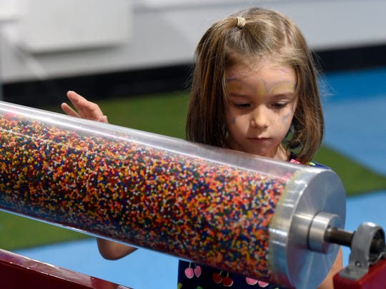 """Lorelai Sauder, 5, of Rockwell, N.C., looks for items hidden by plastic pellets in """"Fantastic Plastic"""" while visiting cMoe in Evansville Tuesday.  cMoe will soon be celebrating its 10th anniversary."""