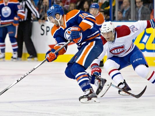 Montreal Canadiens Manny Malhotra (20) chases Edmonton Oilers Teddy Purcell (16) during first period of an NHL hockey game in Edmonton, Alberta, on Monday, Oct. 27, 2014. (AP Photo/The Canadian Press, Jason Franson)