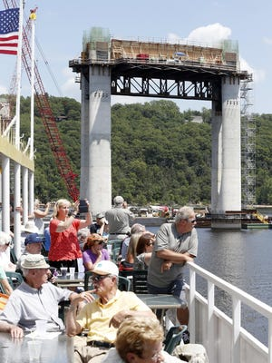 In this July 22, 2015 photo, a pier with Wisconsin in the background towers over the St. Croix River as people pack the top deck of a river boat on a guided tour to view construction of the mile-long St. Croix Crossing bridge linking Minnesota and Wisconsin near Stillwater, Minn. Three times a month, 350 or more people head out on the 90-minute tours, with adults paying $10 apiece for the chance to view one of the biggest and most expensive bridge projects in Minnesota history.