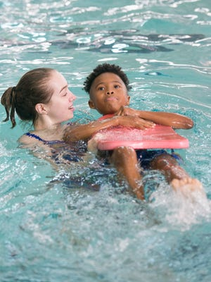 Tate High School swimmer Emily Werkeiser helps Scenic Heights Elementary second-grader Kavonte Hale, 8, float on his back using a kickboard during the Water Safety Day at the University of West Florida Acquatics Center in Pensacola on Friday, May 12, 2017.