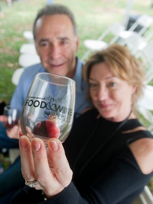 Matt and Kelley Hudzik of Middletown look at a glass of pinot noir they were sampling from the event. 20 October 2017