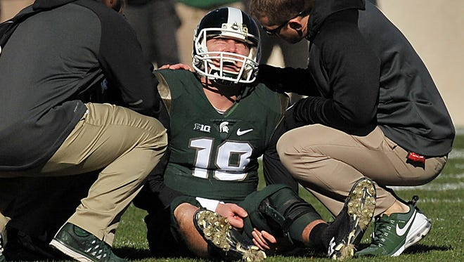 Connor Cook injures his right shoulder on a hit by Maryland defensive end Jesse Aniebonam in the first quarter.