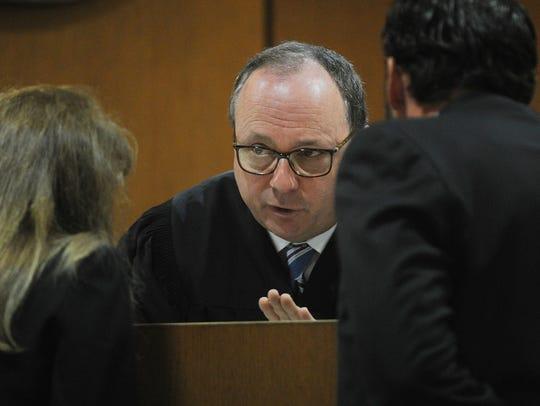 Judge Matthew Guasco, center, talks with Rebecca Day,