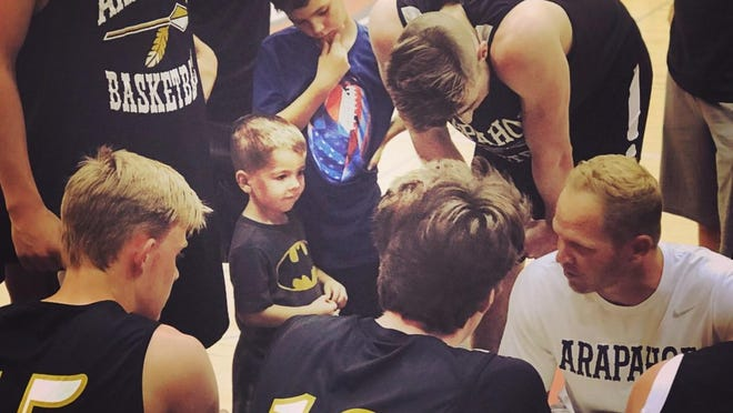 Brad Jansen in the huddle at Arapahoe High School with his team and two of his sons, Cohen and Ezra.