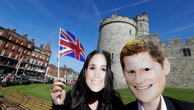 People wearing face masks of Britain's Prince Harry and Meghan Markle pose for a photograph outside Windsor Castle in Windsor, England, Monday, May 14, 2018.