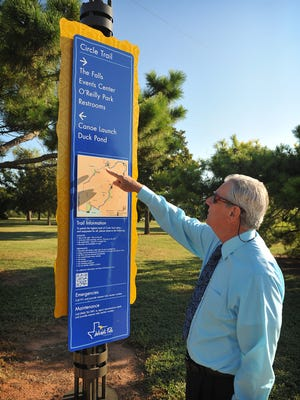 Parks and Recreation Director Jack Murphy points out area s of on one of the city's new way-finding signs in Lucy Park. The city hopes to move forward soon with the next phase of the project.