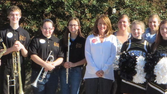 The Stewart County Middle School band and cheeerleaders provide a glitzy black-and-gold Rebel welcome for Tennessee's First Lady Crissy Haslam, pictured with the group, who appeared at the public library on Oct. 15 to promote early reading.