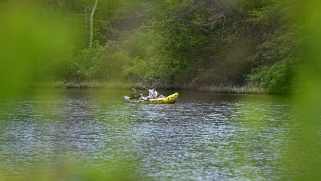 A pair of intrepid fishermen in an inflatable kayak are framed by the underbrush along Shawme Pond in Sandwich.