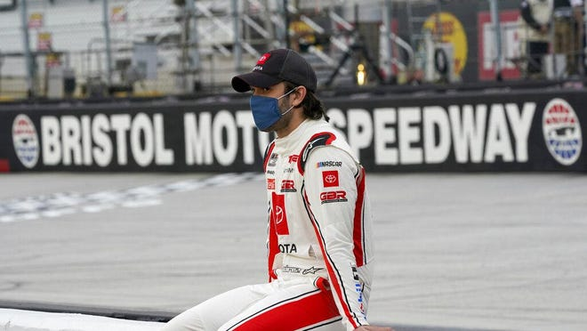 Daniel Suarez sits on a wall along pit row as he waits for driver introductions for the NASCAR Cup Series auto race Saturday, Sept. 19 in Bristol, Tenn.