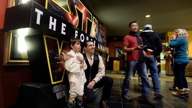 """Chris Geer poses for a photo in front of the Star Wars movie poster with his son Ethan during opening night of """"Star Wars: The Force Awakens"""" at Century Theatre in Boulder, Colo., on Dec. 17, 2015."""
