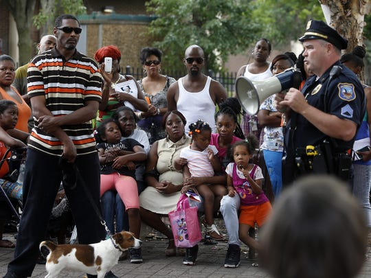 Wilmington police Sgt. Walter Ferris stands in front of family members of shooting victim Crystal Brown as he addresses a prayer vigil at Helen Chambers Park, Thursday evening, July 10, 2014.