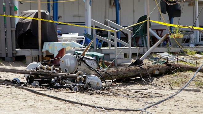 A downed power line lies in the sand in front of damaged cabanas at the Breezy Point Surf Club after a tornado touched down in the area during a severe storm in the Queens section of New York on Sept. 8, 2012.