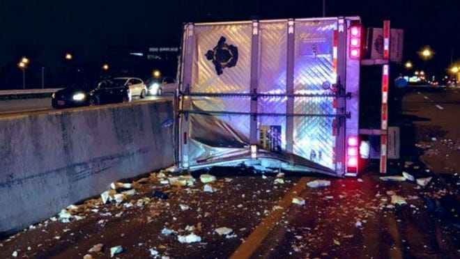A semi lies on its side in the westbound lanes of Interstate 670 Downtown after a crash early Wednesday.