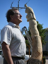 Marco homeowner Steve Hackman stands before the partially completed piece. Hackman commissioned a sculpture of a mermaid carved from the trunk of a Norfolk pine that he cut down in anticipation of Hurricane Irma.