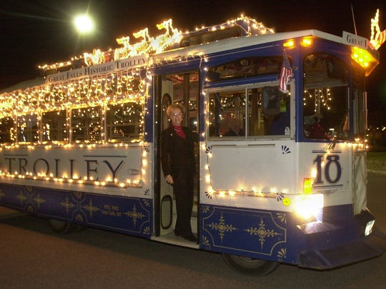Carol Place stands in the doorway to the Great Falls Historic Trolley that has been decorated for the holiday season.
