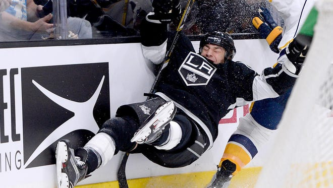 Kings left wing Milan Lucic (17) is checked into the boards by Predators defenseman Shea Weber (6) in the second period Saturday.