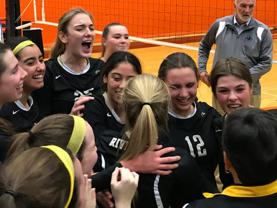 River Dell players surround senior captains Samantha Grandich (12) and Jenna Karpowich (far right, facing) as coach Dianne Furusawa hands them the Group 2 girls volleyball championship trophy on Saturday, Nov. 11, 2017 at William Paterson University.