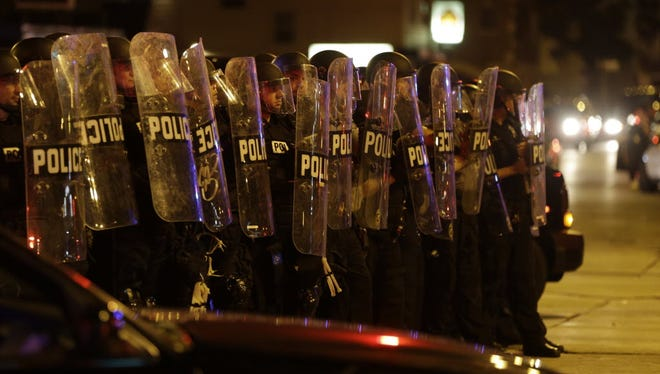 Police move in on a crowd throwing rocks at police in Milwaukee, Sunday, Aug. 14, 2016.