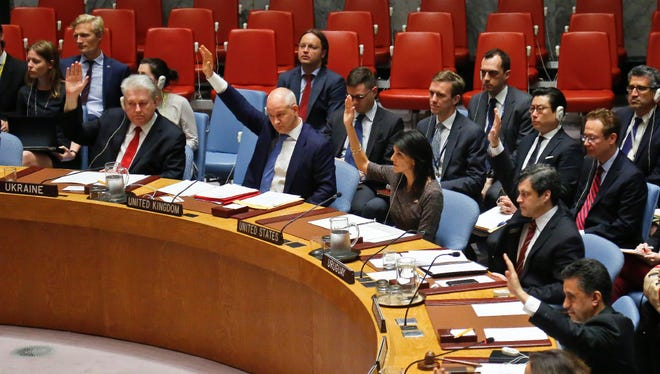 Ambassadors to the United Nations raise hands in a Security Council resolution vote to sanction North Korea on Friday.