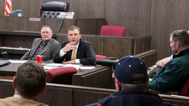 Iron County Commissioner Dave Miller answers questions asked by volunteer firefighter Thomas Cluff during a hearing on Monday, March 9, 2015. At the hearing, the commissioners voted to sell the county's ambulance service to Gold Cross.