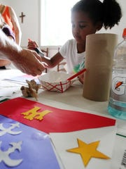 Corinne DeBlanc, 5, makes her own Acadian flag Sunday during Acadian Culture Day at Vermilionville in 2013