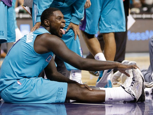 Charlotte Hornets' Lance Stephenson reacts as he stretches his injured leg during the second half of an NBA basketball game against the Milwaukee Bucks in Charlotte, N.C., Wednesday, Oct. 29, 2014. The Hornets won 108-106 in overtime. (AP Photo/Chuck Burton)