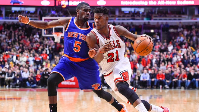 Chicago Bulls guard Jimmy Butler (21) dribbles the ball against New York Knicks guard Tim Hardaway Jr. (5) during the second half at United Center.