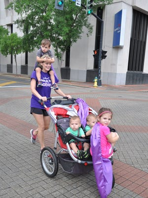 Frannie Beebe walks with son Drew while pushing twins Jake and Pearce and daughter Amelia in a stroller during the Alexandria March for Babies. The annual walk benefits the March of Dimes organization, which supports families with premature babies and funds research to prevent early births. Beebe's three sons all were born premature and spent weeks in the newborn intensive care unit.