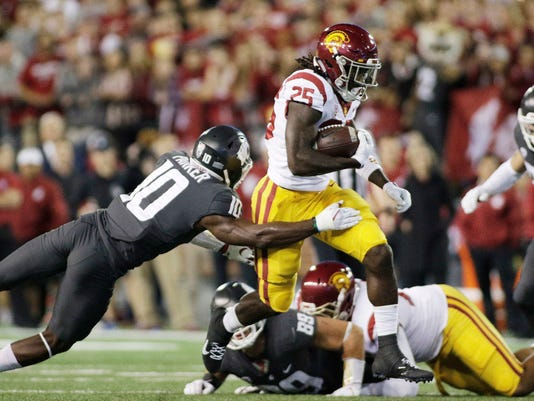 Southern California tailback Ronald Jones II (25) breaks a tackle by Washington State defensive back Kirkland Parker (10) during the first half of an NCAA college football game in Pullman, Wash., Friday, Sept. 29, 2017. (AP Photo/Young Kwak)