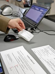 An election official works with absentee ballots in this file photo from 2012.