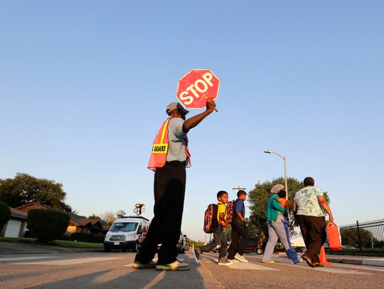Crossing guard Frank Dewalt helps students and parents
